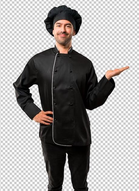 Homem de chef de uniforme preto segurando copyspace imaginário na palma da mão para inserir um anúncio Psd Premium