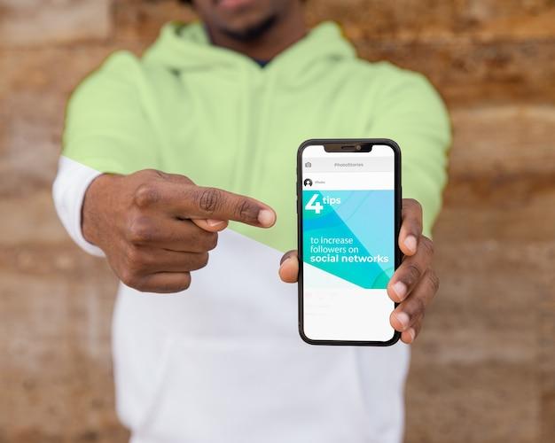 Homem de close-up com capuz mostrando móvel Psd grátis