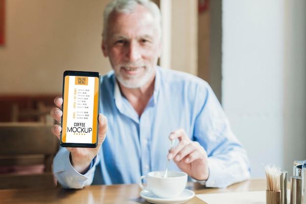 Homem de frente para a cafeteria segurando uma maquete de celular Psd grátis