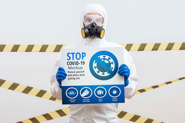 Homem de terno hazmat segurando um mock-up de coronavírus de parada Psd grátis