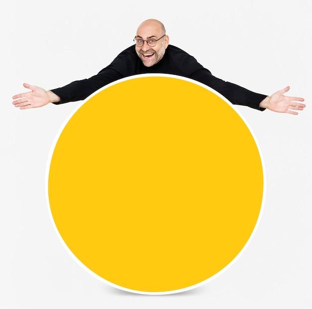 Homem feliz, mostrando uma placa amarela redonda Psd grátis