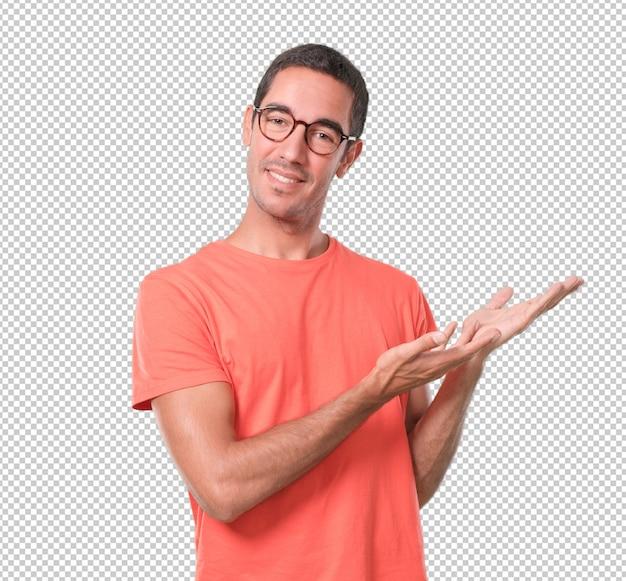 Homem jovem confiante mostrando algo com a mão Psd Premium
