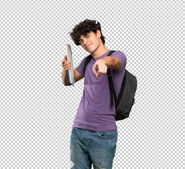 Homem jovem estudante aponta o dedo para você enquanto sorrindo Psd Premium