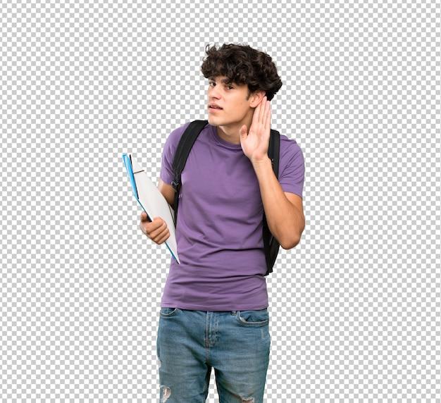 Homem jovem estudante ouvindo algo, colocando a mão na orelha Psd Premium