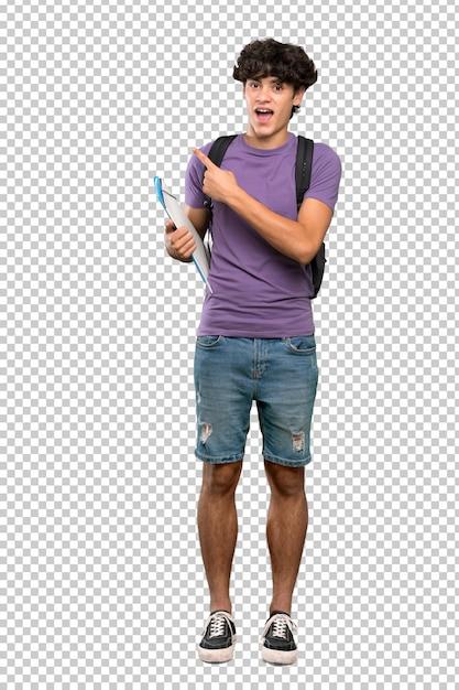 Homem jovem estudante surpreso e apontando o lado Psd Premium