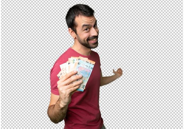 Homem levando muito dinheiro apontando para trás e apresentando um produto Psd Premium
