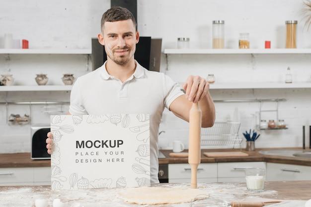 Homem na cozinha segurando o rolo de massa Psd grátis