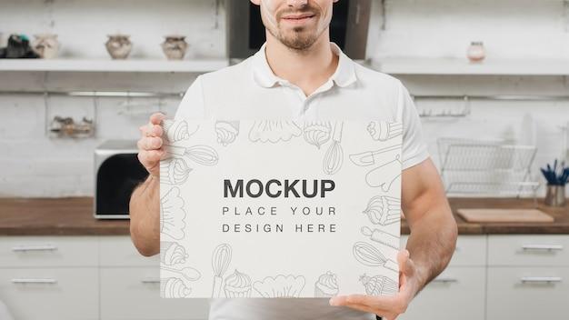 Homem na cozinha segurando um cartaz em branco Psd grátis