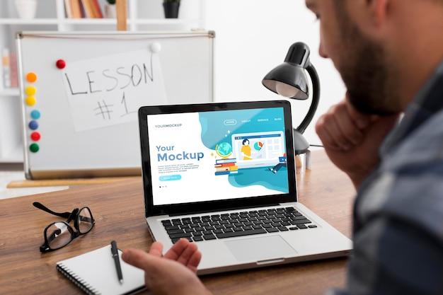 Homem na mesa com modelo de laptop Psd grátis