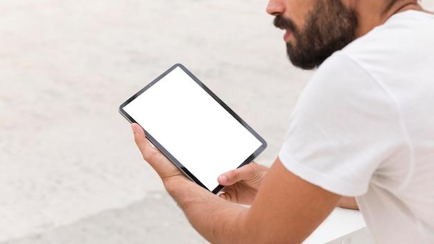 Homem na rua com tablet lendo online Psd grátis
