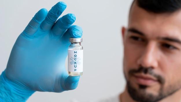 Homem olhando para um frasco de vacina Psd grátis