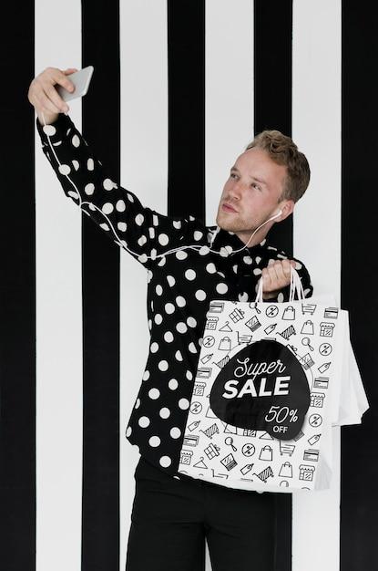 Homem satisfeito tomando selfie com sacolas de compras Psd grátis
