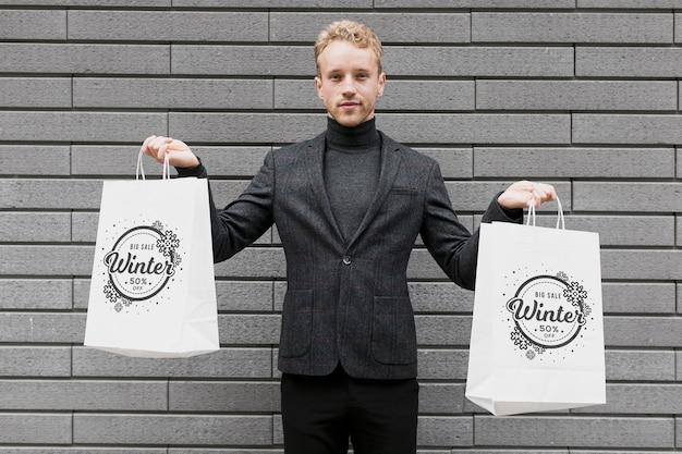 Homem segurando em cada mão sacos de compras Psd grátis