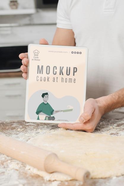 Homem segurando um livro enquanto rola massa na cozinha Psd grátis