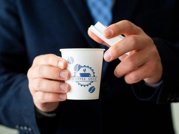 Homem segurando um modelo de xícara de chá Psd grátis