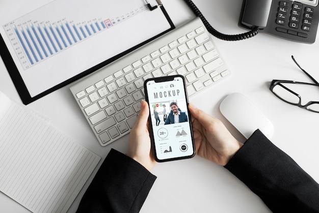 Homem segurando uma maquete de smartphone no escritório Psd grátis