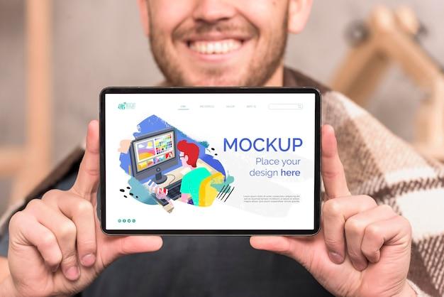 Homem sorridente mostrando maquete digital de tablet Psd grátis