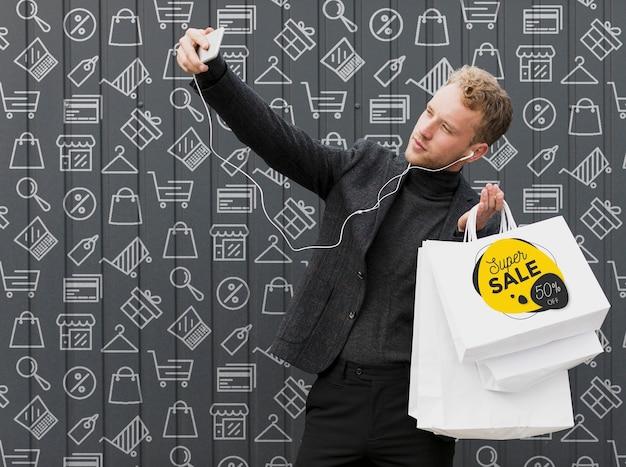 Homem sorridente tomando selfie com suas compras Psd grátis