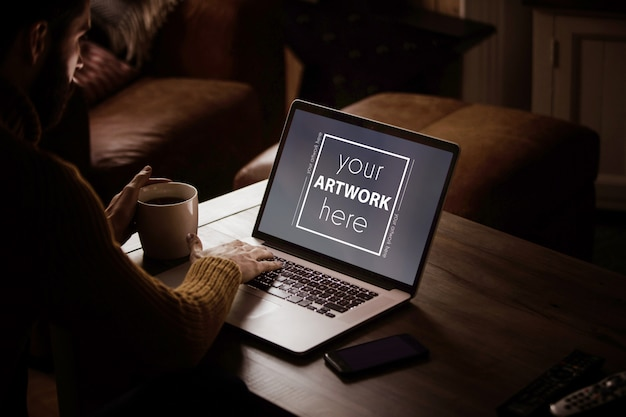 Homem usando laptop com xícara de café na mesa Psd Premium