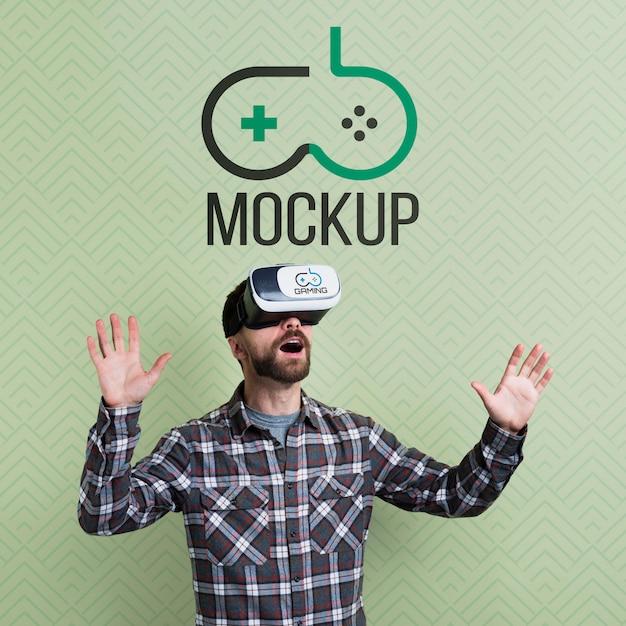 Homem usando um fone de ouvido de realidade virtual e mock-up médio Psd grátis