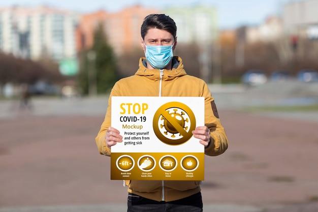 Homem vestindo uma máscara segurando um modelo de parada de coronavírus Psd grátis