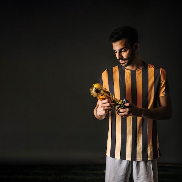 Jogador de futebol, olhando troféu Psd grátis