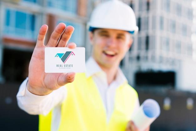 Jovem arquiteto segurando um cartão de visita Psd grátis