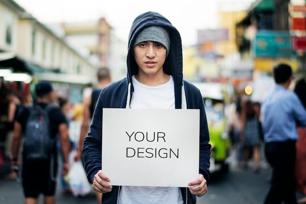 Jovem, asiático, homem, segurando, vazio, painél publicitário, ao ar livre Psd grátis