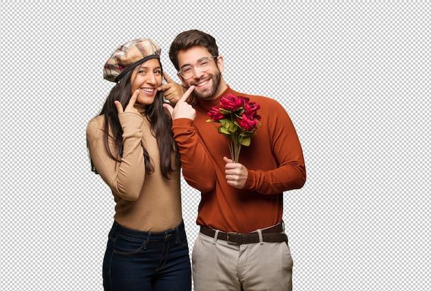 Jovem casal em dia dos namorados sorri, apontando a boca Psd Premium