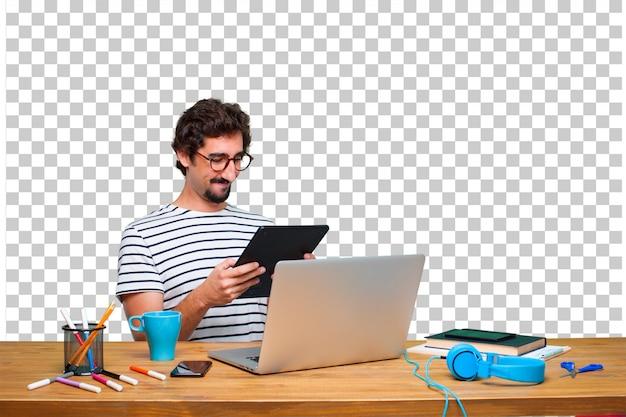 Jovem designer gráfico louco em uma mesa com um laptop e com um tablet de tela de toque Psd Premium