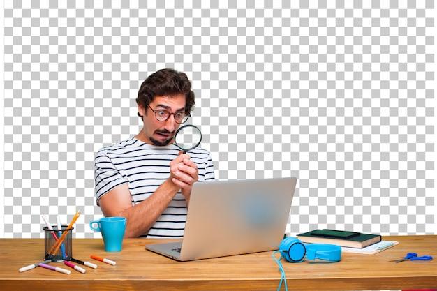 Jovem designer gráfico louco em uma mesa com um laptop e com uma lupa Psd Premium