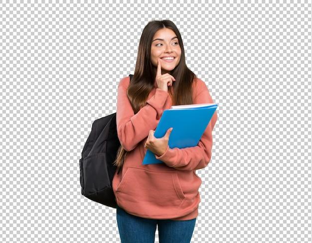 Jovem, estudante, mulher segura, cadernos, pensando, um, idéia, enquanto, olhar Psd Premium