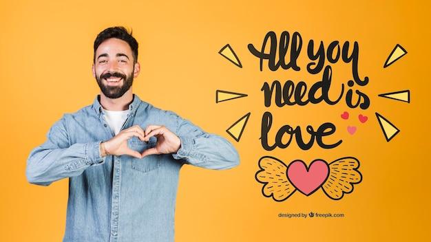 Jovem feliz fazendo um coração com as mãos ao lado de amor citação Psd grátis
