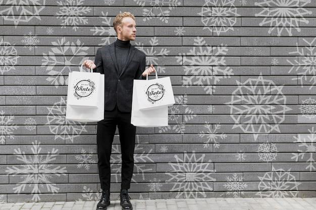 Jovem macho segurando sacolas de compras Psd grátis
