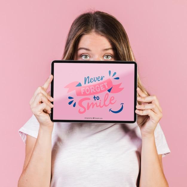Jovem mulher cobrindo o rosto até os olhos com uma maquete de tablet Psd grátis