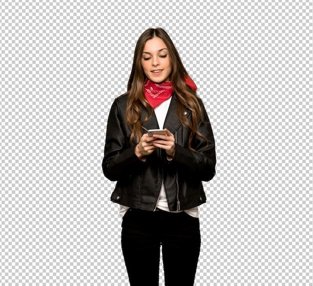 Jovem mulher com jaqueta de couro, enviando uma mensagem com o celular Psd Premium