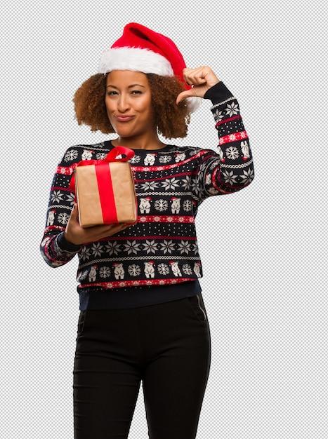 Jovem negra segurando um presente no dia de natal, apontando os dedos, exemplo a seguir Psd Premium