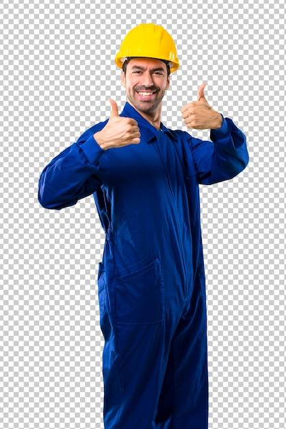 Jovem trabalhador com capacete dando um polegar para cima gesto e sorrindo porque teve sucesso Psd Premium