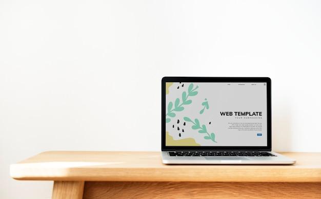 Laptop mostrando o modelo de site em uma mesa de madeira Psd grátis