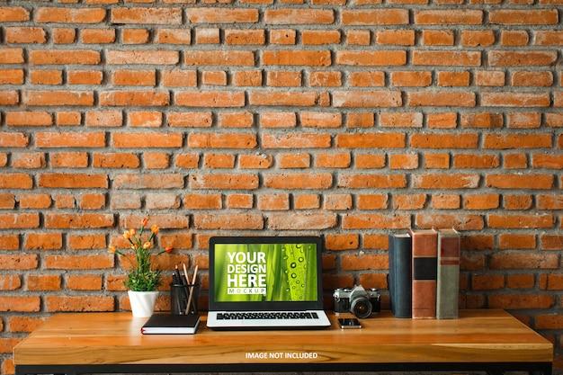 Laptop na mesa de madeira e maquete da parede de tijolo Psd Premium
