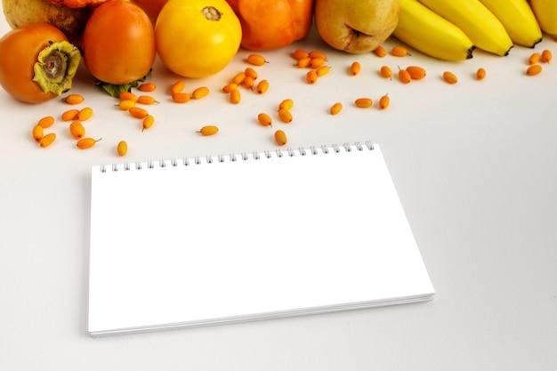 Legumes frescos amarelos e alaranjados do outono e frutas e caderno Psd Premium