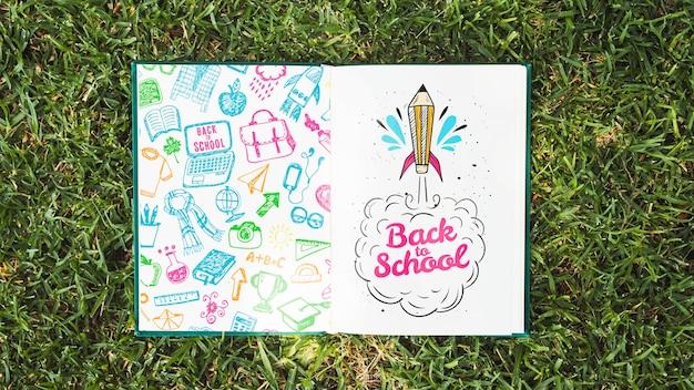 Livro colorido na grama mock-up Psd grátis