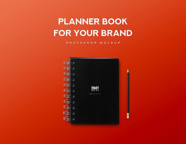 Livro de planejador para sua marca e lápis preto sobre fundo vermelho Psd Premium