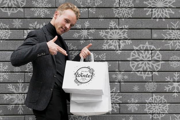Macho feliz, apontando para seus sacos de compras Psd grátis