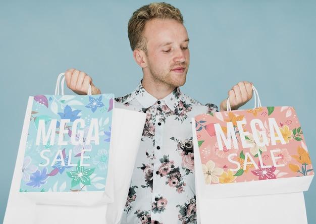 Macho novo que verifica sacos de compras Psd grátis