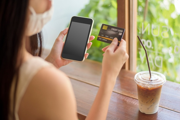 Mão de mulher está segurando maquete de telefone celular com cartão de crédito Psd Premium