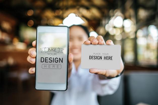 Mão de mulher segura maquete de smartphone e cartão de crédito psd Psd grátis