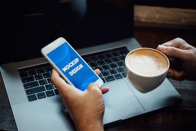 Mão do homem de negócios usando o portátil e o telefone celular que trabalham em linha na cafetaria na luz da manhã. Psd Premium