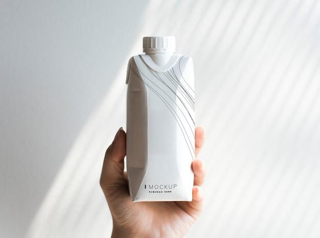 Mão humana segurando maquete de garrafa de papel Psd grátis