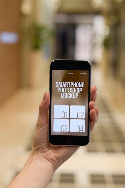 Mão humana segurando smartphone moderno + Psd Premium